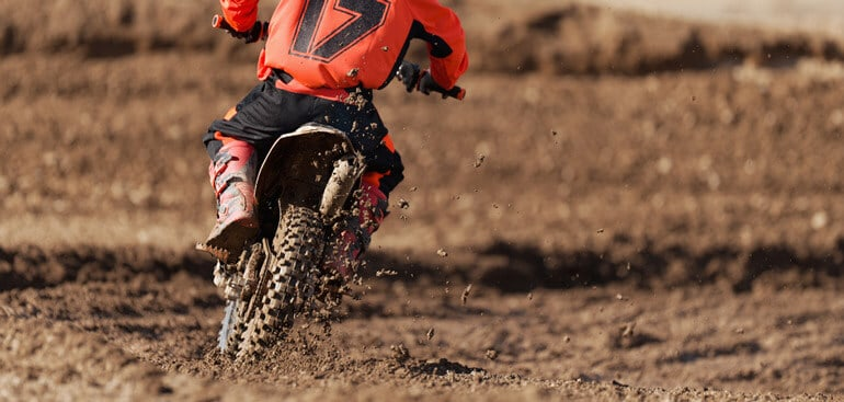 Child on motorcycle participates in motocross race