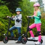 boy and girl are riding electric scooters