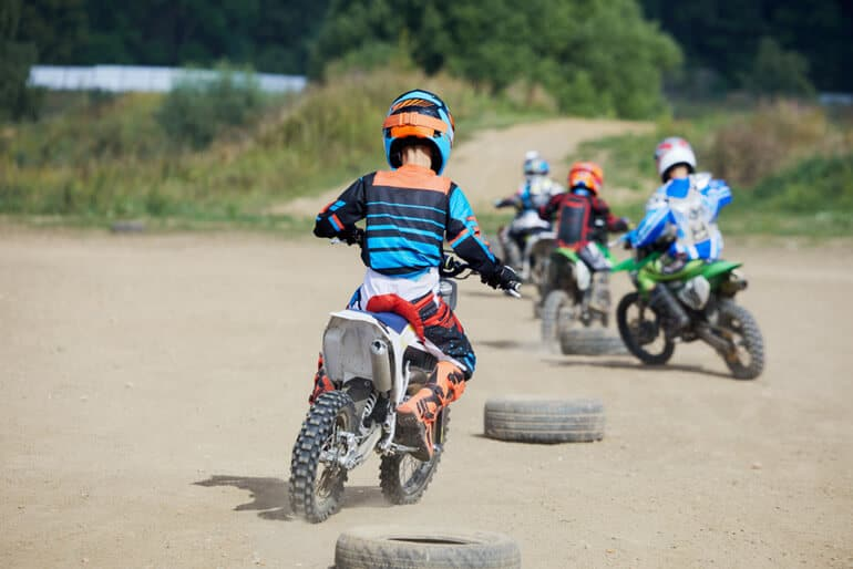 boy are having fun on dirt bikes back view