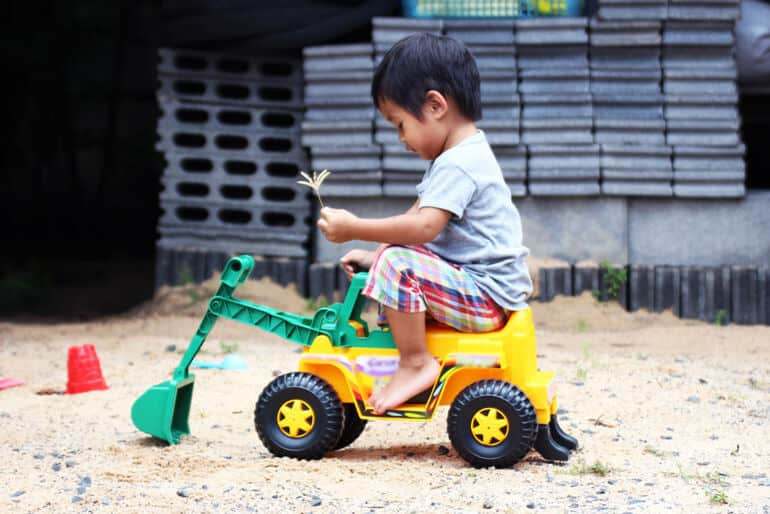 boy drives plastic truck toy car