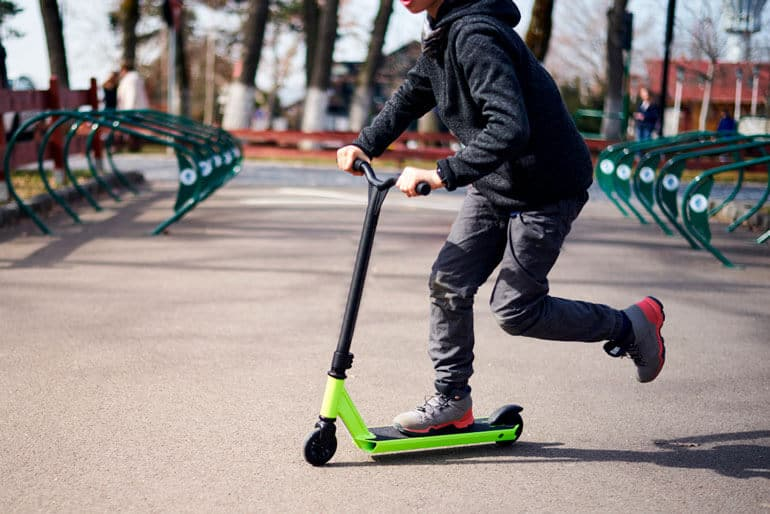 boy in hoodie riding green scooter