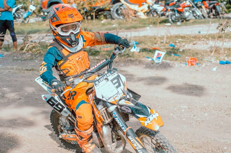 boy in orange gear is riding a dirt bike