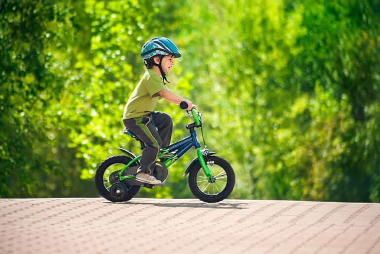 boy is laughing while riding a bike
