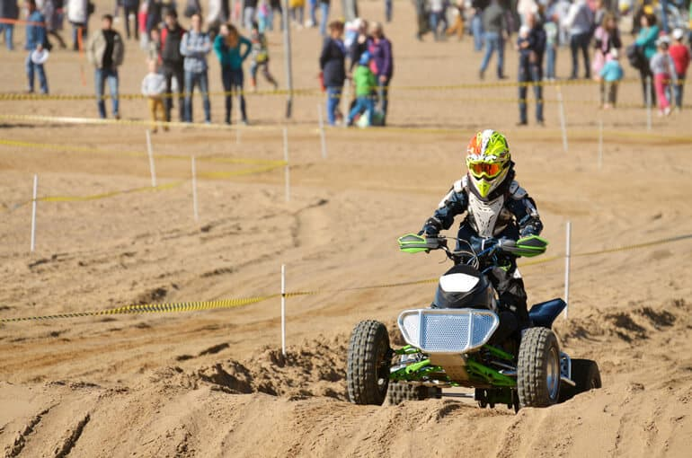 boy is traversing the track on his four wheeler