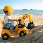 boy play a excavator toy on the beach