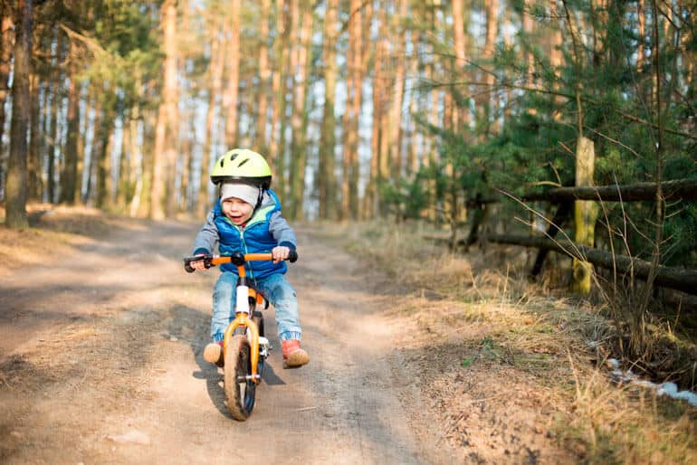 boy riding balance bike off road