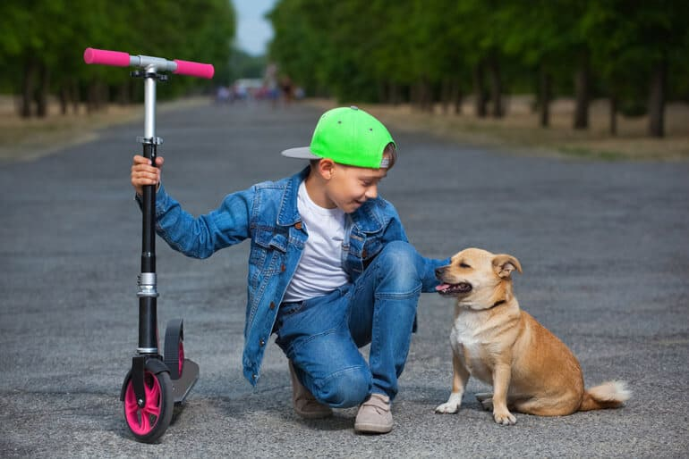 boy with scooter petting dog