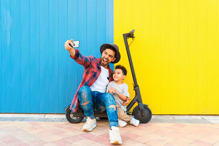 father and son taking selfie on scooter