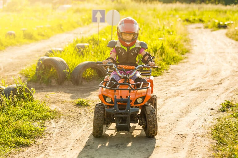 girl fully equipped riding four wheeler