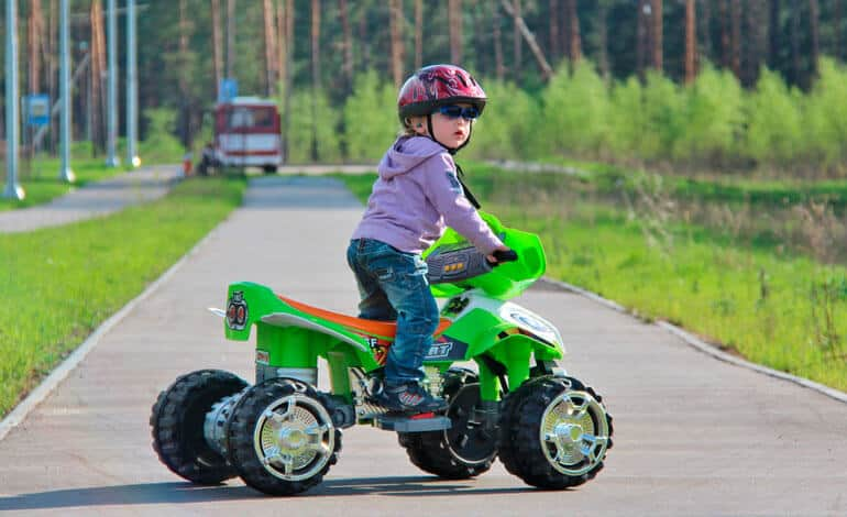 girl in helmet riding green atv