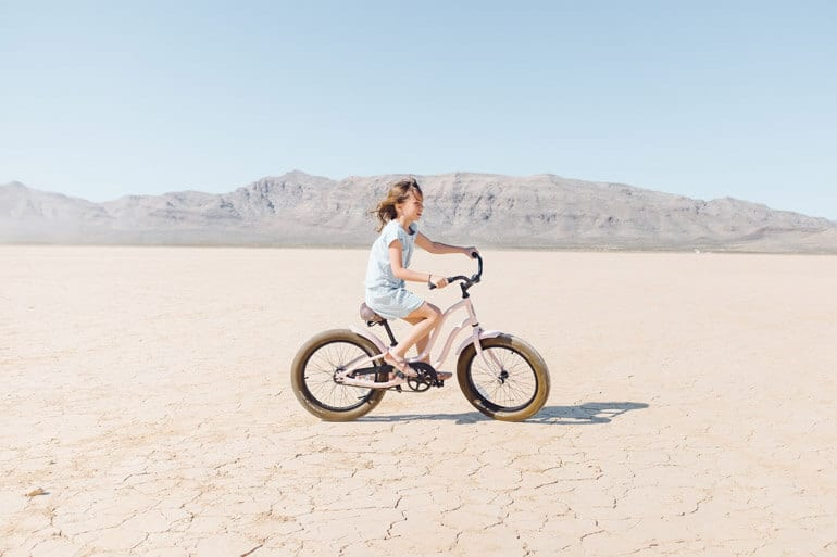 girl is riding a pink bike in desert