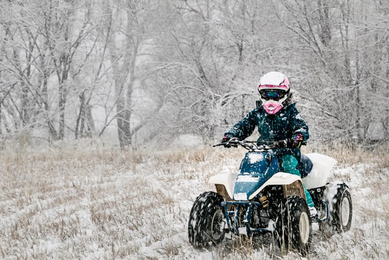 girl is riding an ATV in winter