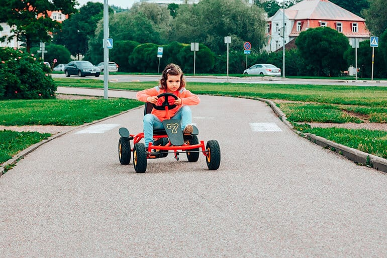 girl is riding red go kart