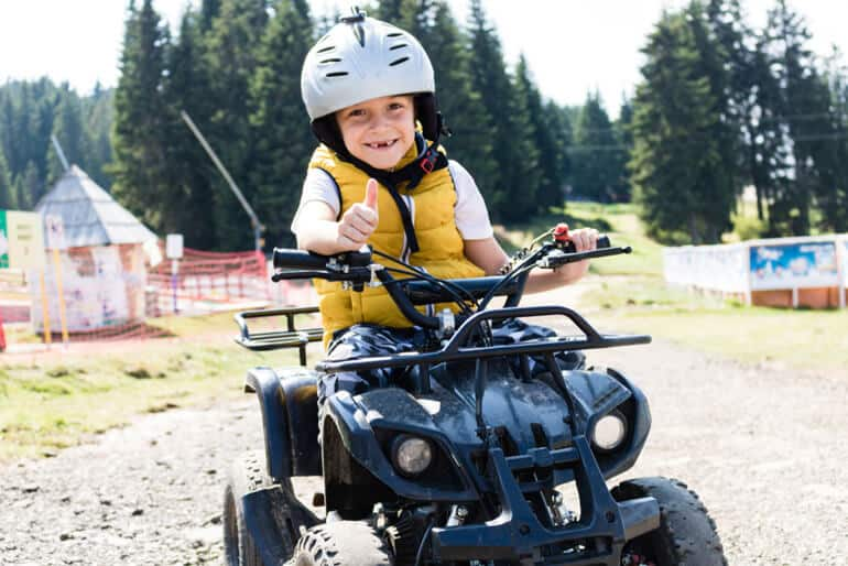 happy boy shows thumbs up in atv