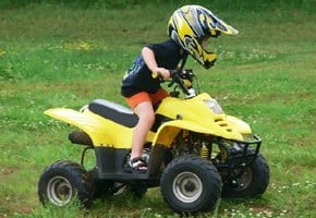 Kid riding four ATV in helmet