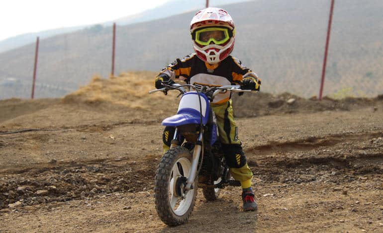 little boy is posing on an off-road bike