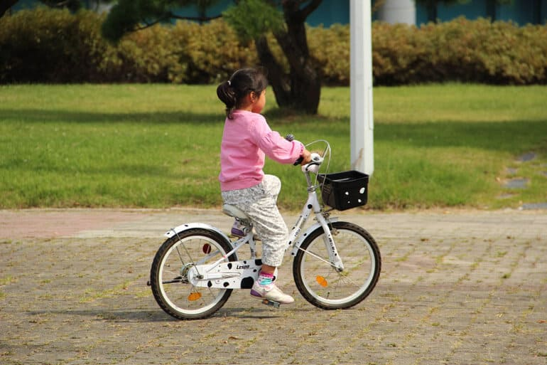 little girl is sitting on a white pedal bike