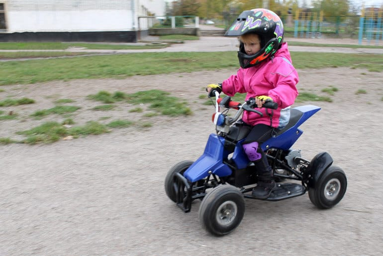 little girl with pink jacket riding four-wheeler