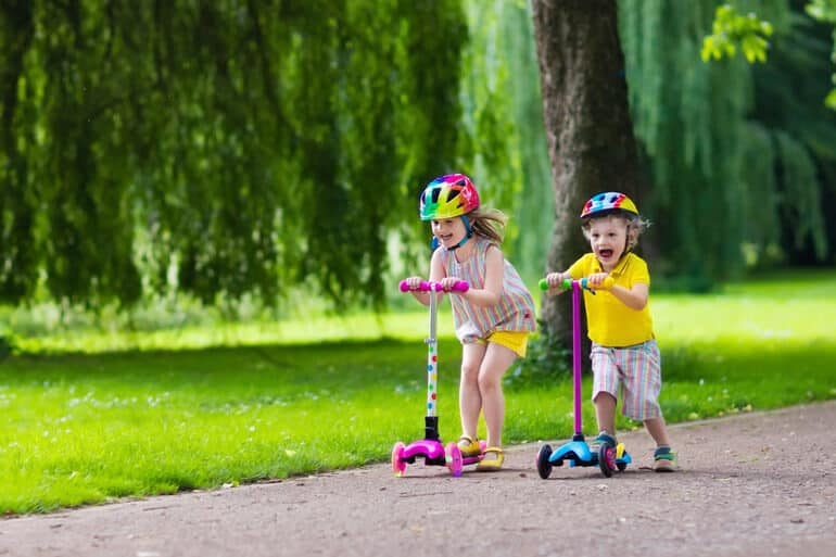 sibling riding scooters in park