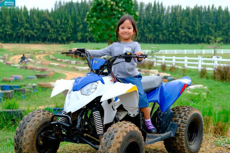 young girl sitting in atv